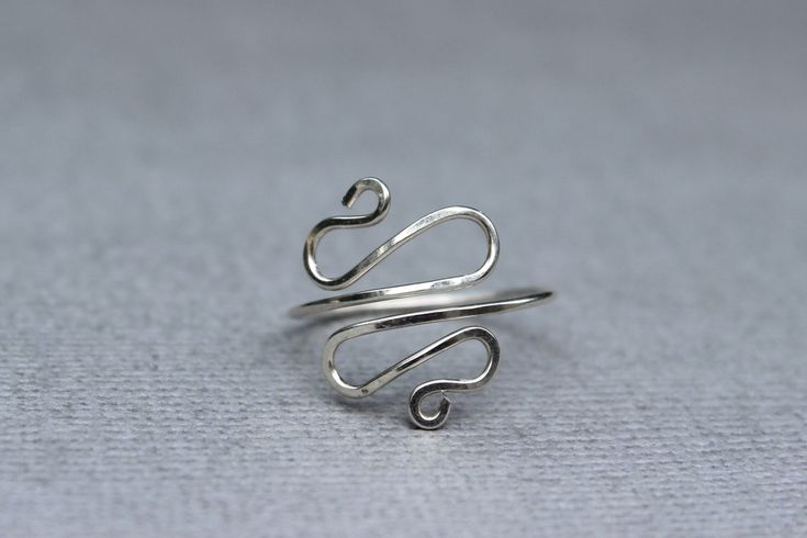 A ring wired for elegance. This is a wire ring shaped in symmetric swirls. The perfect simple statement ring. The ring is hammered for texture and strength.This ring can be made out of sterling silver