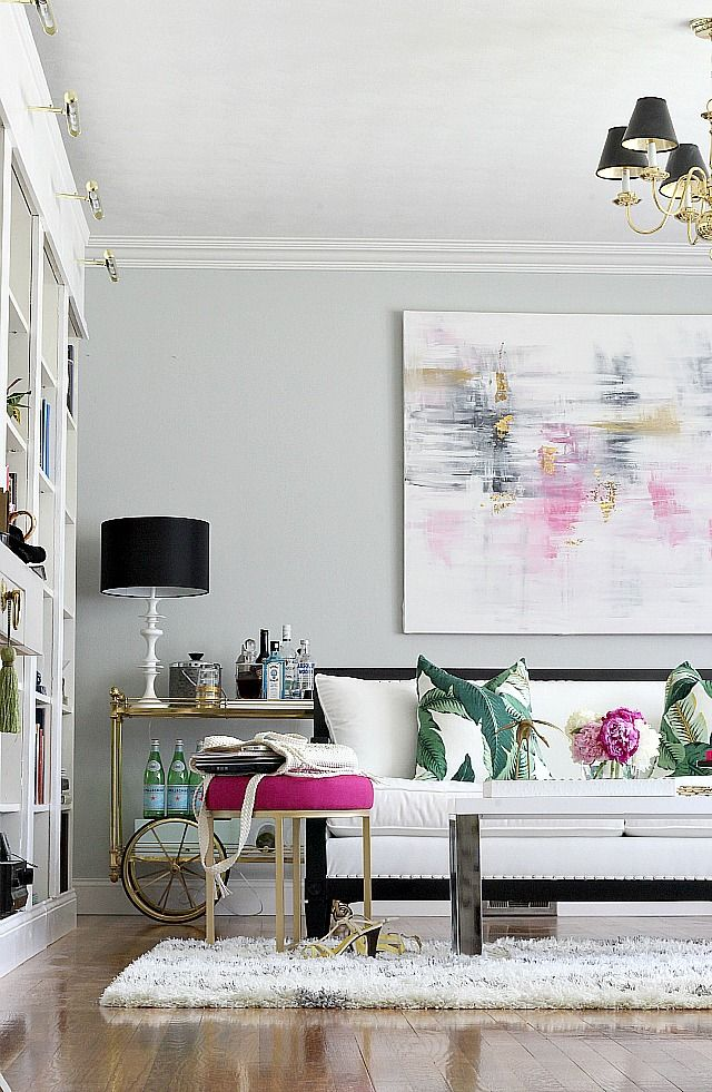 A summer living room with diy bookcases, diy abstract art, pops of bright color, a mix of modern and vintage thrifted finds.