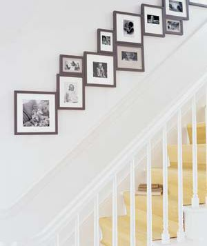 "A new take on a staircase wall gallery: ""Lining a staircase with family photos is a classic tactic, but you can really give them impact by making a tight arrangement in frames of the same style and color, in three or four sizes."""