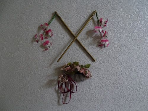 Two fast-food chopsticks were painted gold; small holes were drilled to accommodate swinging fuchsias.  A small arrangement of flowers and ribbon on a comb was also prepared.
