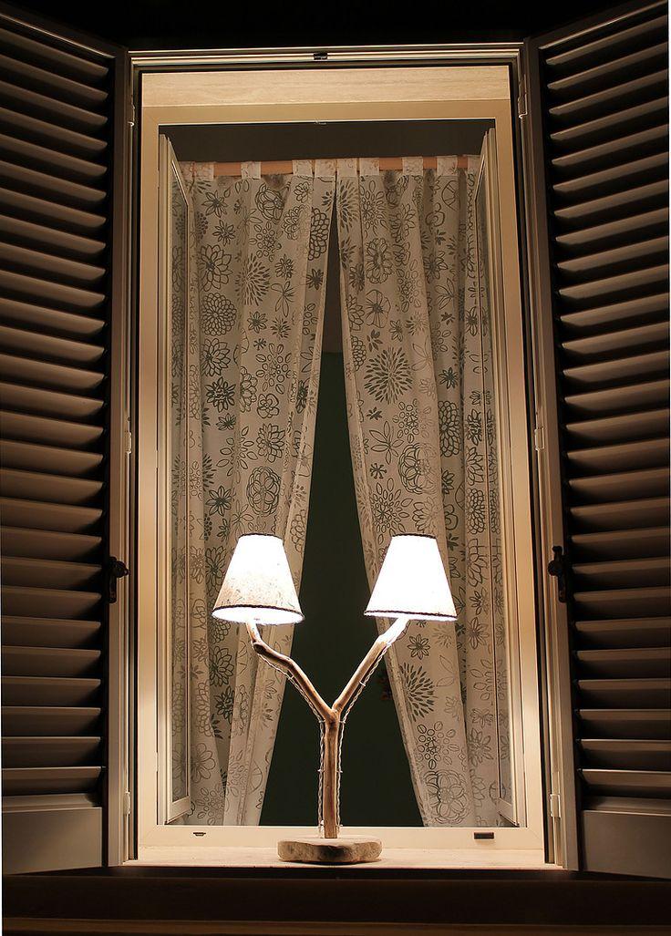 Tete-à-tete: lampada da tavolo in legno di mare con base in pietra leccese sagomata a scalpello. Paralume rivestito di carta di gelso con inserti naturali e passamaneria in filo carta intrecciato.