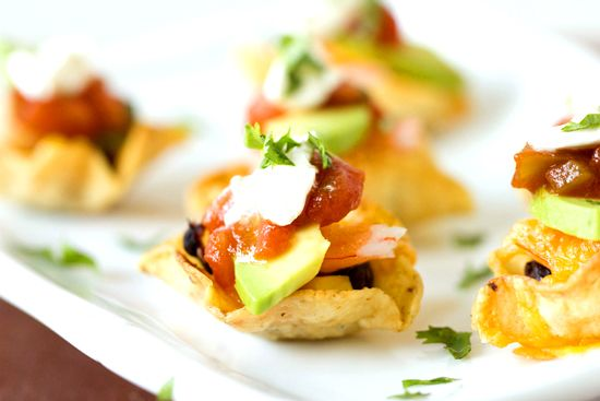 Shrimp Nacho Bites     >>>40-50 scoop-shaped tortilla chips  1 cup black beans  1 cup corn, fresh or frozen  40 pieces small frozen, deveined shrimp, thawed and tails removed  1 cup shredded cheddar or Monterey Jack cheese (or a combination)  1 avocado, sliced into 1-inch pieces  ½ cup salsa  ½ cup sour cream  ½ cup cilantro, finely chopped