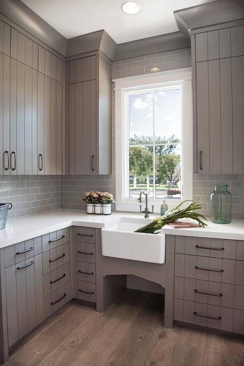 Stunning gray laundry room is equipped with a farmhouse sink with an antique hook and spout faucet fixed to a white quartz countertop beneath a window framed by gray subway backsplash tiles.