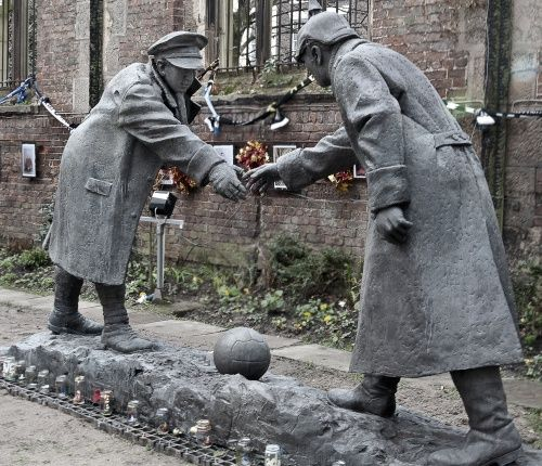 "This is a statue by Andy Edwards entitled ""All Together Now"" which for the next few days will be on display in St Luke's, Liverpool's famous ""bombed out church"". The figures are about to shake hands standing over a football which relates to the time that British and German soldiers paused, apparently to play football on Christmas Day 1914. The hands do not quite meet which allows one to place a hand between them, joining the act of all too brief sanity on that day. The figures will leave…"