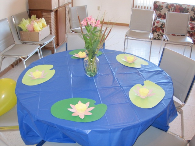 Frog themed baby shower. These are my ponds with lily pad cut out of green placemats. Lotus flowers cut from cardstock with yellow cup cake liners filled with home-made chocolate frogs. Cat-tails make up the center pieces.