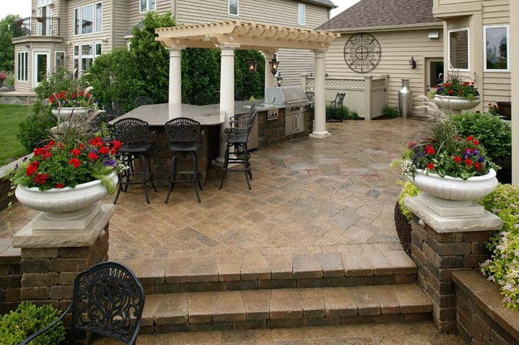 This Italian-inspired patio, pergola, and planting design has old-world elegance, yet fits into the modern world with sleek stonework and furnishings. Design by JR's Creative Landscaping in Naperville, Il.