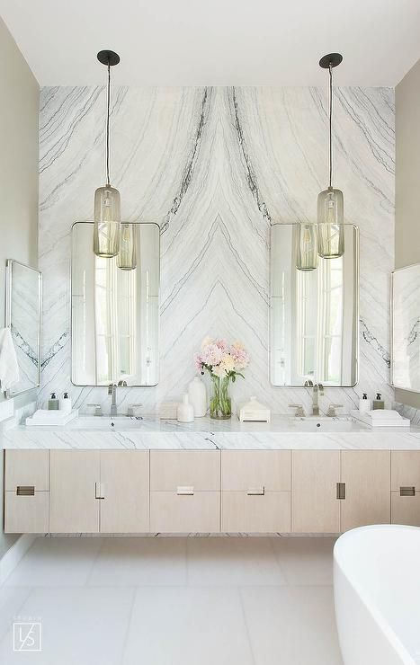 A pair of matching gray glass vanity pendants compliments a classic, traditional style with a long cylindrical shape suspended by black chain mounted over a marble countertop.