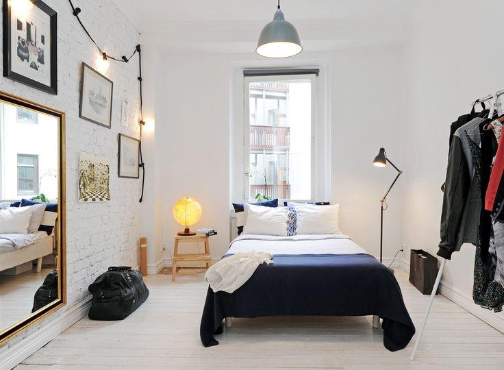 Arrangements du mur gauche: mur de briques blanches, grand miroir installé bas, cadres au-dessus, guirlande de lumières au-dessus.
