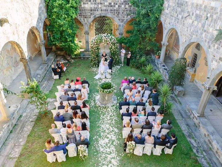 A beautiful Florence castle courtyard wedding ceremony with an arch of pink roses for Samantha and Simon - see more wedding details, decor ideas for your destination wedding abroad and photos on the Wedding Ideas website!