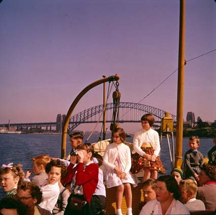 Children on ferry with Sydney Harbour Bridge in background, 1961. NAA: A1500, K6521