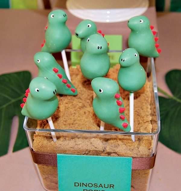 Dino-mite! Dinosaur Birthday Party with cute green dinosaur cake pops, a T-Rex cake topper with candy dinosaur eggs, & wooden fossil decorations!