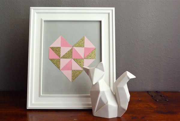 Triângulos isósceles cortados em três tipos de papéis diferentes formam esse coração moderninho. Cole os triângulos formando um coração ângulo sobre o papel de fundo neutro. A moldura deve combinar com a casa e com o desenho, sem roubar a atenção.