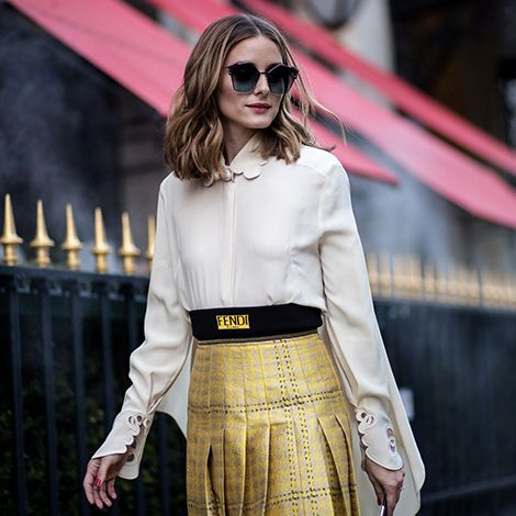 Classically feminine. That was the look of the day for Olivia while attending the Fendi Fall 2017 Haute Couture show. A perfectly pressed box pleated midi skirt with a slim thigh-high slit is paire…