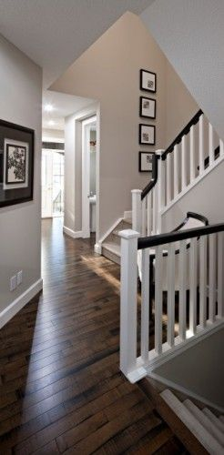 White banister poles with a dark wood handrail and matching stained floor make this space look brilliant, beige/grey walls are the perfect colour to complement the wood