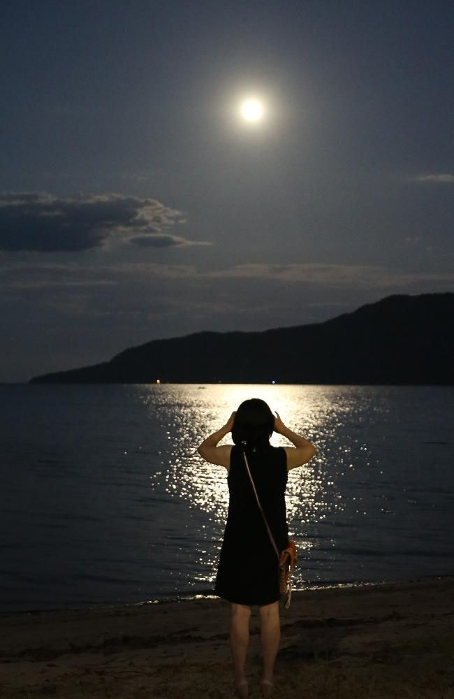 A tourist in Cairns snaps the moon which is 30 per cent brighter than usual. Picture: JUSTIN BRIERTY