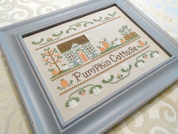 This beautiful cross-stitched art piece features a fall-theme country cottage surrounded by pumpkins and flowers making it a beautiful home decor accessory.    Rustic grey frame measures approxmately 9 x 11 inches and has an easel-back and sawtooth hanger so you can choose whether to hang it on a wall or use it as a tabletop centerpiece. Inside 8 x 10 inch design has been hand-stitched over many hours on 28 count lambswool linen using beautifully colored cotton fibers.    All items in my…