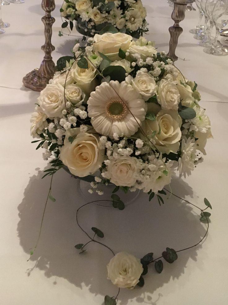 Bordsdekoration i olika vita blommor, gjord i låg glasskål på fot.
