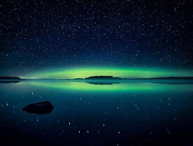 A green arch under a couple of stars. Finland. Photo by Timo Oksanen