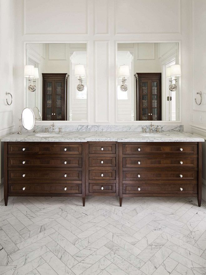 Luxurious bathroom design with marble tile in herringbone pattern. Dark wood double vanities and twin tall glass doored cabinets. Design by The Fox Group. #thefoxgroup #luxurybath #herringbonetile