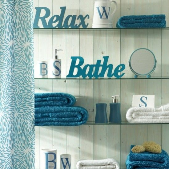 Cool teal bathroom, glass shelves and white 3-d words