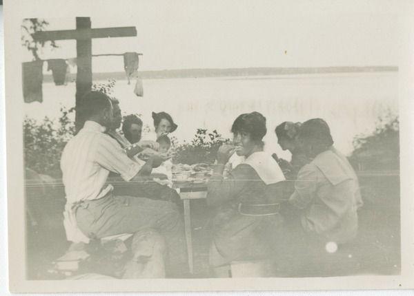 [Group eating around table next to lake] | saskhistoryonline.ca