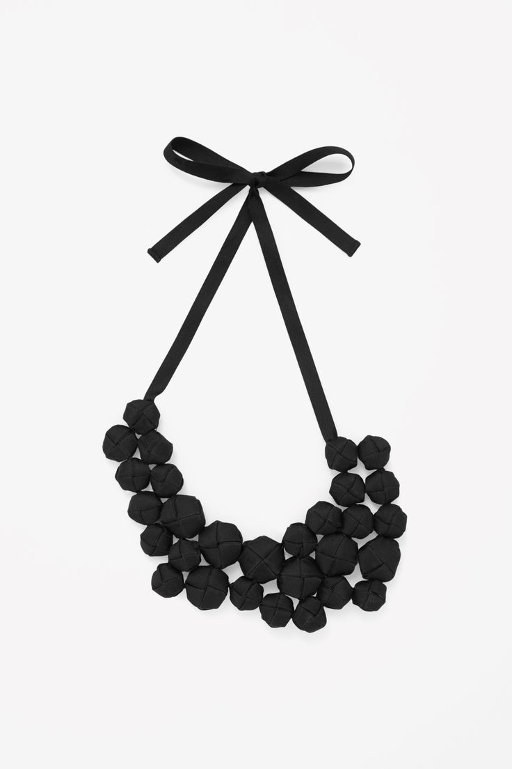 This necklace, secured with a fabric tie fastening, has grosgrain ribbon covered beads.