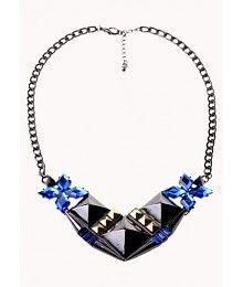 Statement ketting met verstelbare sluiting in de nek. De ketting is versierd met drie zwarte stenen in piramide vorm, studs en blauwe imitatie steentjes. De statement ketting is gemaakt van hoogwaardig zink.