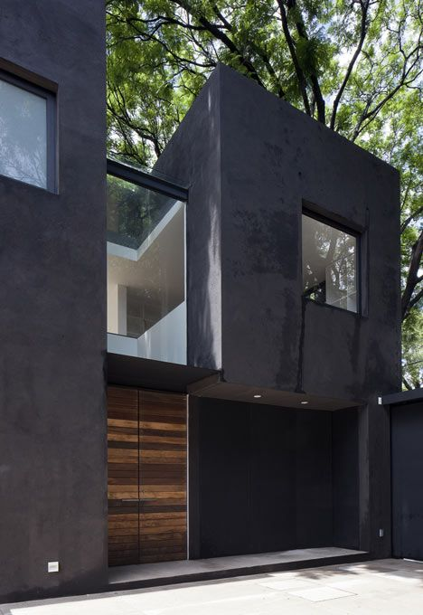A high-walled courtyard runs parallel to this long black house in Mexico City