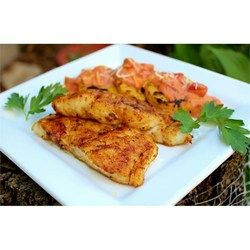 Firm white cod fillets are seasoned with Cajun spice mix and lemon pepper before being grilled over hot coals. A lemon-butter sauce is basted onto the fish as it cooks.