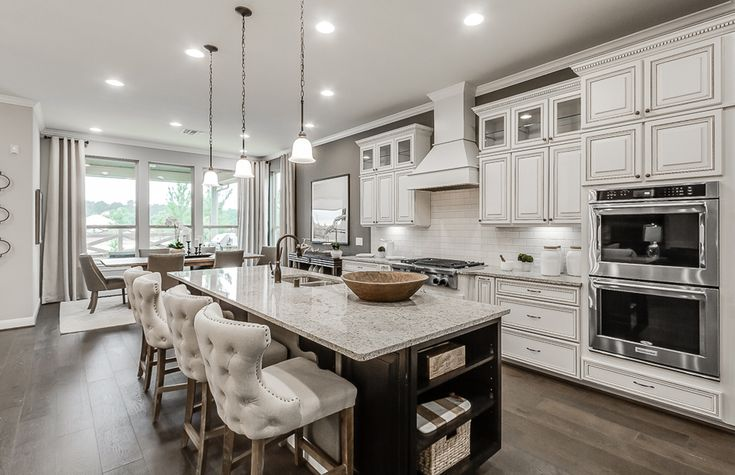 This modern kitchen's white cabinets and subway tile contrast perfectly against the gray walls. | Pulte Homes