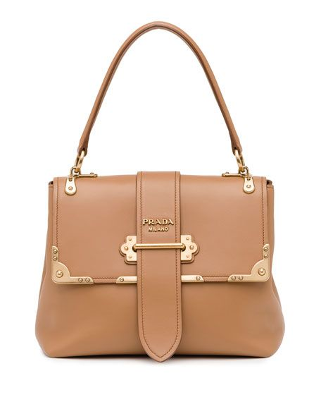 "Prada smooth calf leather tote bag. Golden hardware. Flat top handle with rings. Half-flap top with tab closure. Logo lettering at center. Divided interior, leather lining; one flap pocket. 7.9""H x 10"