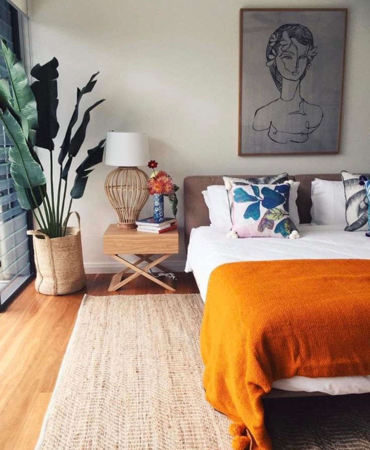 Boho bedroom ideas. Going boho with white, orange throw, plant, bedside table, floral cushions, portrait over bed