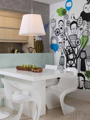 Da Desmobilia, as cadeiras Panton (à dir.), de Verner Panton, e Lucite (à esq.), de Steen Ostergaard, fazem parceria com a mesa de laca. O balcão forrado de vidro, entre a cozinha e a sala de jantar, serve de aparador. Imagem divertida: assinado pela designer alemã Antonia Kuehn, o adesivo da parede, da Diz Decor, foi encontrado pela moradora na internet. Fruteira da A Lot Of e pendente do Laboratório da Luz. Projeto de Carla Basiches.