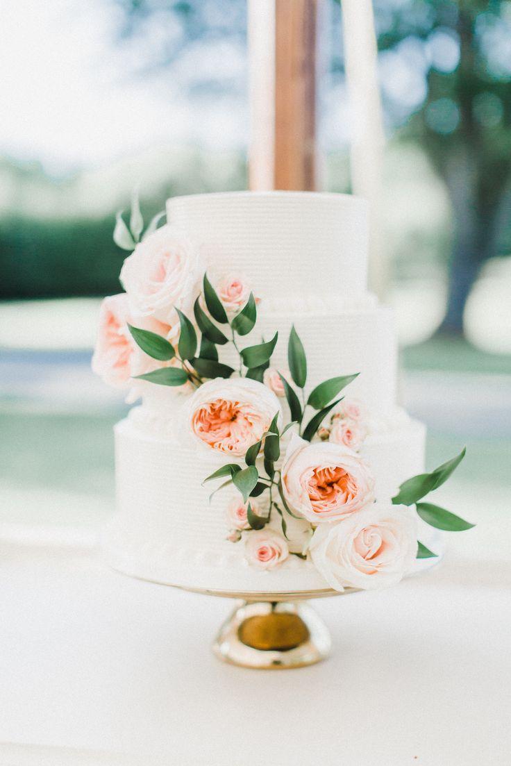 White buttercream wedding cake with cascading fresh flowers