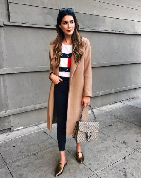 A Tommy Hilfiger tee with a coat, cropped jeans, and loafers.