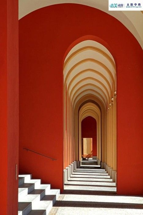 Love this look…. an arched long hallway with doors set enfilade, and walls painted a rich, deep orange
