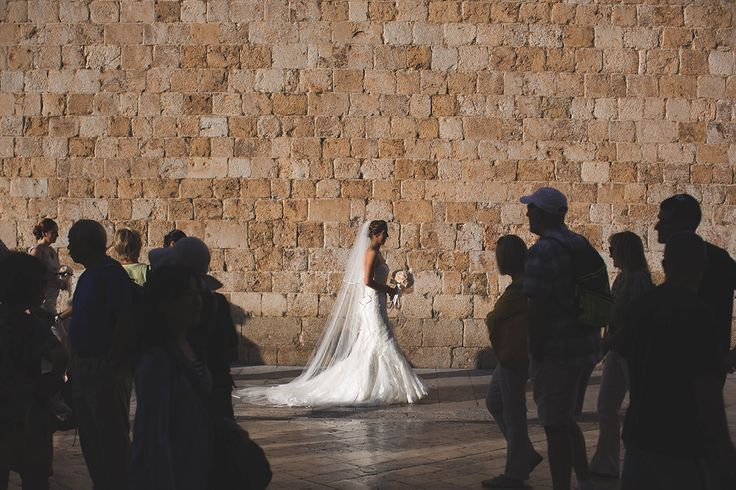 One of a set of images taken at this chic destination Wedding of Jenna & Nick. The stylish old town of Dubrovnik, Croatia.  The Bride walks down the street.  Photography by Matt Porteous
