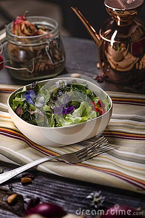 Colorfull Salad with Edible Flowers over a dark wooden table