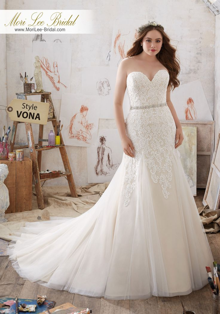 Style VONA Mila Wedding Dress  This Glamorous Fit & Flare Wedding Gown Features Frosted Alençon Lace AppliquŽés on Net. A Crystal Beaded Waistband and Soft Godet Pleats Add a Romantic Touch. Colors Available: White, Ivory, Ivory/Coco. Shown in Ivory/Coco.