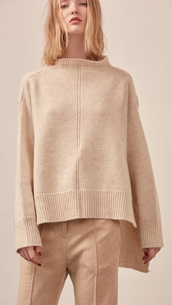 The Erin Sweater in soft oatmeal. Features rolled neckline, long sleeves, drop shoulder, side slits. Pull on. Relaxed silhouette.    CO\MPOSITION AND CARE Hand