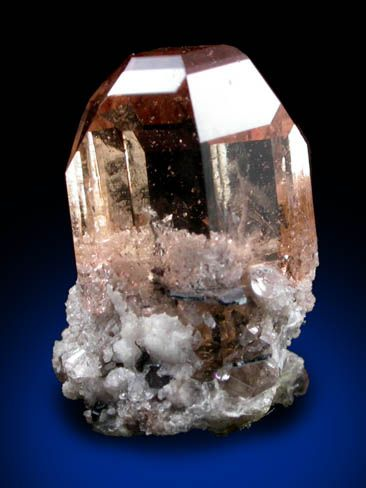 Topaz from Topaz Mountain, Juab County, Utah Lustrous transparent crystal of sherry-colored topaz with minor matrix attached at the base. There are two crystals intergrown in parallel orientation. The topaz crystal is internally flawless in the upper half. Ex. A. Stevenson (1916-2007)