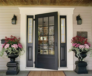 Front door of a house with symmetrical windows, lighting and large flower pot decor adds curb appeal.