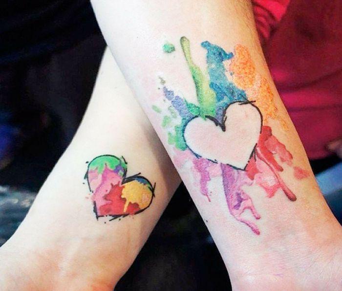 tatuajes de hermanas, tatuajes originales de color en la muñeca, corazón en explosión de colores estilo acuarela, tatuajes parecidas pero no iguales