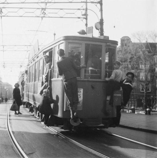 Amsterdam: De Muiderstraat in de jaren net na de oorlog toen meeliften op de tram heel gewoon was.
