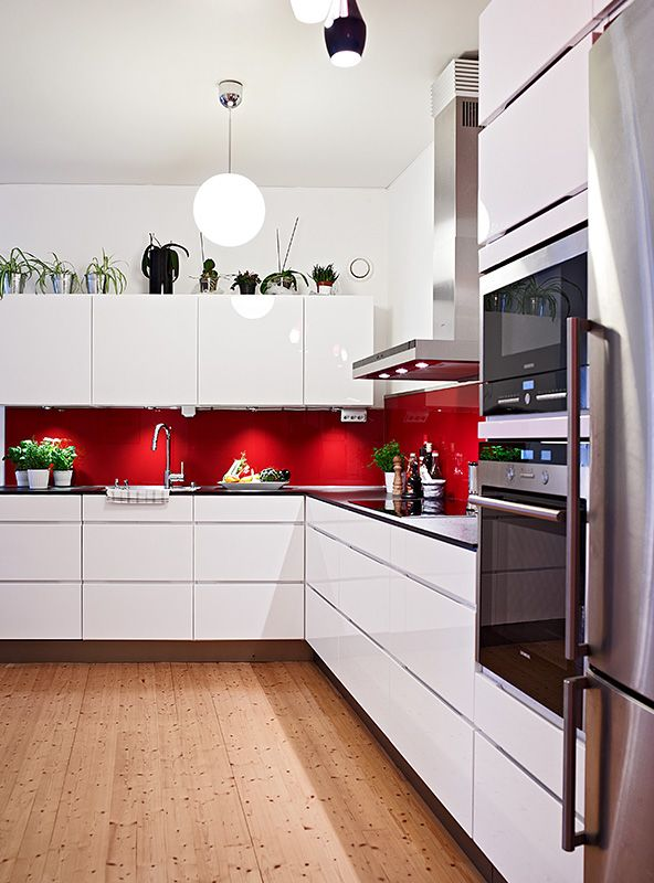 Red splashback white cabinets silver appliances and wooden for Red white and black kitchen designs