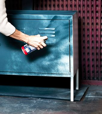 A woman spray paints a white metal cabinet blue.