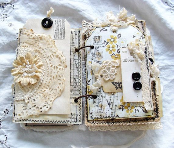 Unique vintage inspired junk journal with soft cover..... Book covers constructed from black and tan floral burlap lined with tan muslin. Front cover featuring a handmade fabric and lace flower with a rhinestone center and an organza bow. Inside front cover has a sheer pocket that holds a tag and tiny booklet. One generous length of torn organza is sewn to the back cover and wraps around a button on the front for tying it closed. Iv used antique bronze grommets on the front and back cover…
