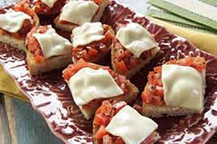 Cheesy Bruschetta. Toasted bread slices are topped with a mix of tomato, garlic, olive oil and basil. Melted mozzarella blankets it all for an irresistible appetizer.