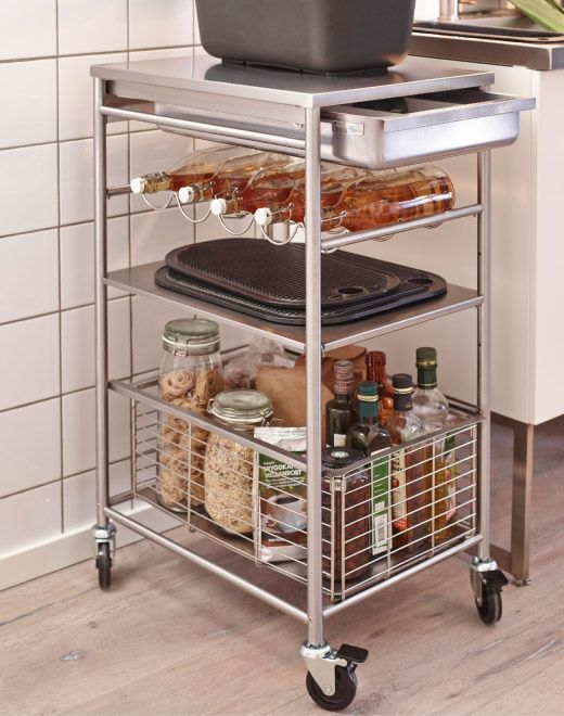 Stainless steel kitchen trolley loaded with bottles and glass jars