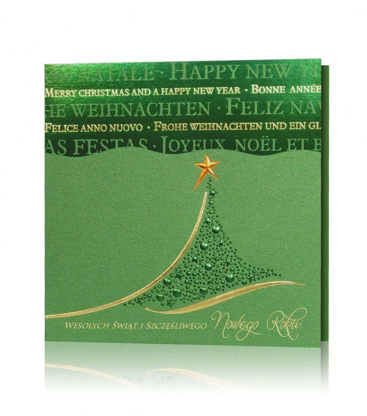 Kartka świąteczna B 817 Zielony metaliczny papier, złoty, zielony, miedziany nadruk. Przepiękny motyw choinki świątecznej jest utworzony z błyszczących gwiazdek oraz bombek, całość obramowana złotymi liniami. W górnej części kartki nadrukowane teksty w różnych językach.